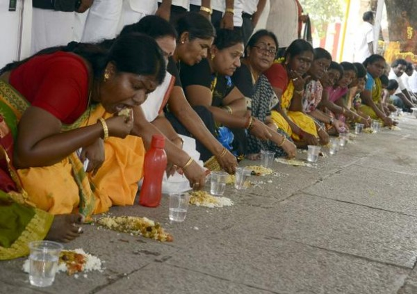P. Karthiyayini, Mayor of Vellore (left) along with other AIADMK volunteers eating 'Mann Soru' at the Selliamman Temple in Vellore. They were praying for the release of former Chief Minister Jayalalithaa. Photo:C. Venkatachalapathy-courtesy: The Hindu