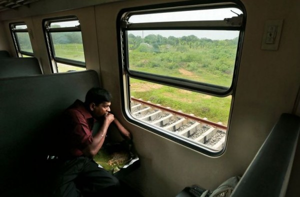 A Sinhalese man eating on a train on a trip to the north of Sri Lanka in October. The Tamil-dominated north is a popular destination, but some there do not welcome the visitors. Credit Eranga Jayawardena/Associated Press-courtesy: NYTimes.com
