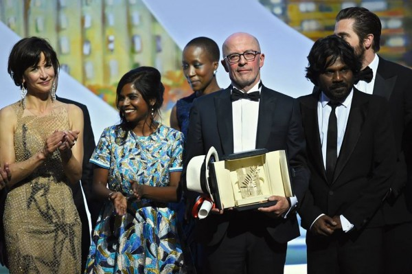 """French director Jacques Audiard (C) poses on stage with French actress and member of the Feature Film jury Sophie Marceau (L), Sri Lankan actress Kalieaswari Srinivasan (2ndL) and Sri Lankan actor Jesuthasan Antonythasan after being awarded with the Palme d'Or from his film """"Dheepan"""" during the closing ceremony of the 68th Cannes Film Festival in Cannes, southeastern France, on May 24, 2015. AFP PHOTO / ANNE-CHRISTINE POUJOULAT-via:"""