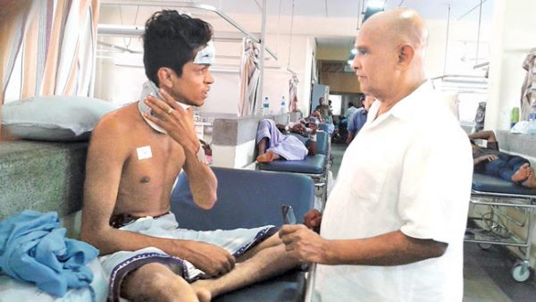 Northern Province Governor Reginald Cooray visiting injured Sinhala student in hospital ~ via dailynews.lk